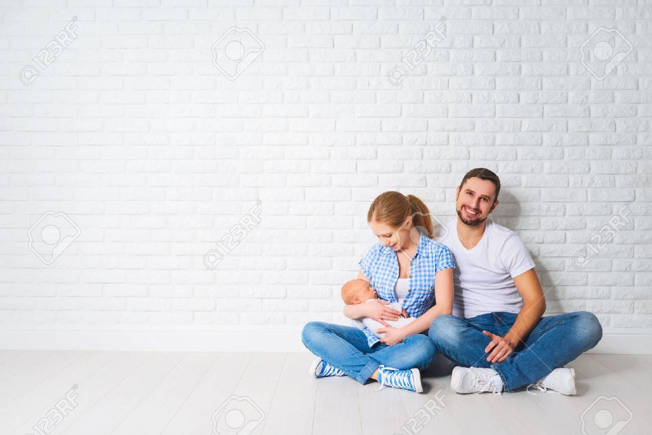 madre de familia feliz y padre de un bebé recién nacido que se sienta en el suelo cerca de la pared de ladrillo en blanco Foto de archivo - 51980862