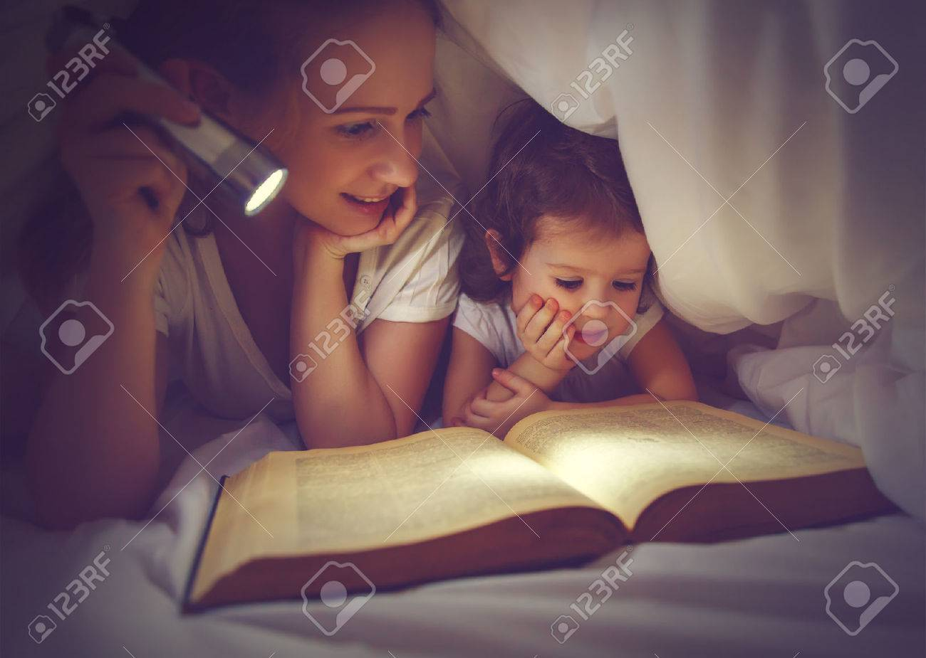 Family reading bedtime. Mom and child daughter reading a book with a flashlight under the blanket in bed - 53116226