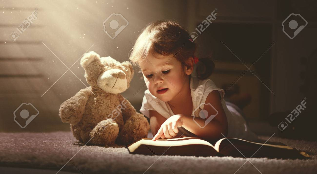 child little girl reading a magic book in the dark home with a toy teddy bear - 54007523