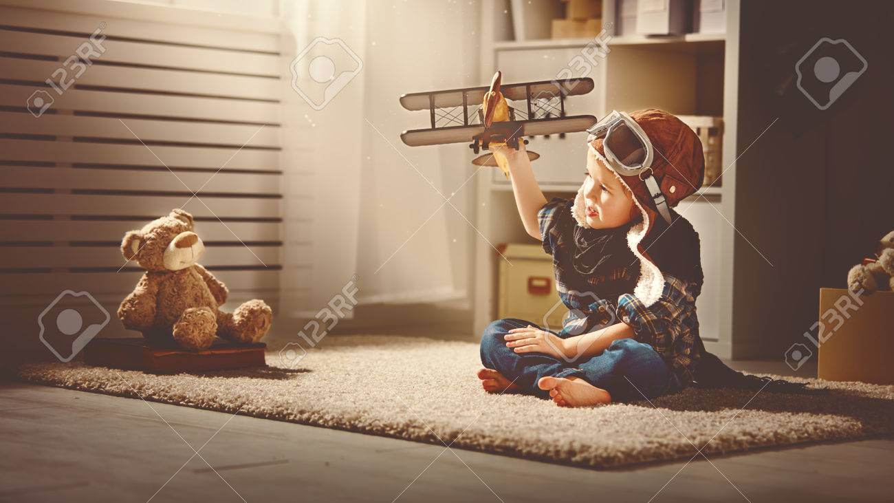 concept of children's dreams and travels. pilot aviator child with a toy airplane plays at home in his room - 54007524