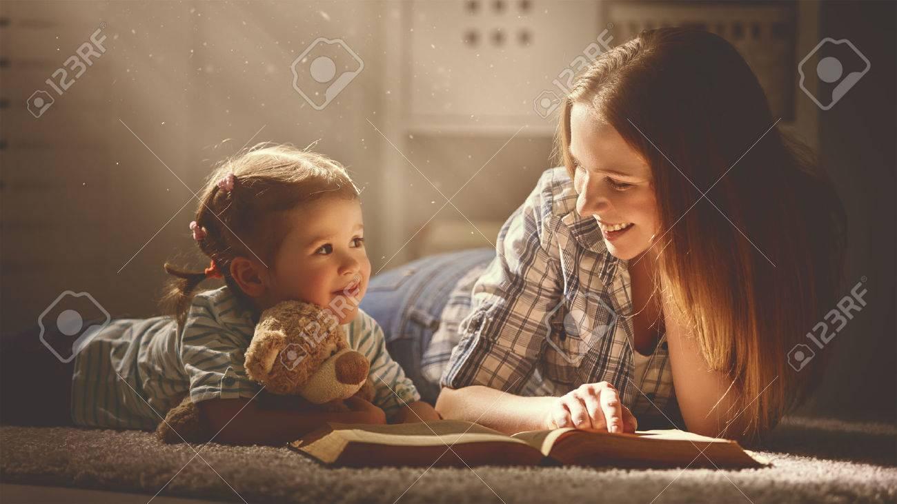 madre de familia feliz y la hija leyeron un libro en la tarde en casa Foto de archivo - 54007526
