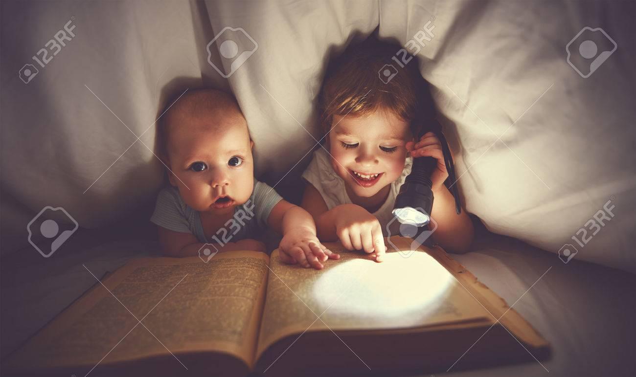 niños hermano y hermana leen un libro con aflashlight bajo la manta en la cama Foto de archivo - 54119341
