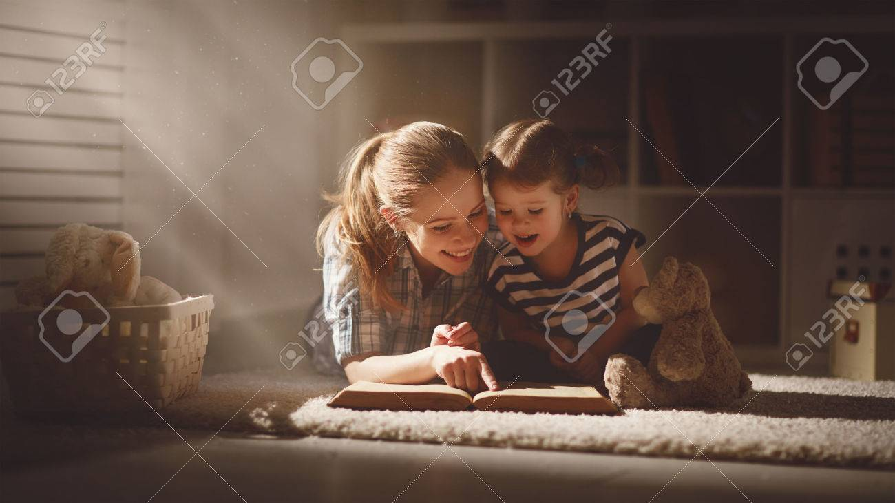 happy family mother and daughter read a book in the evening at home - 55011085