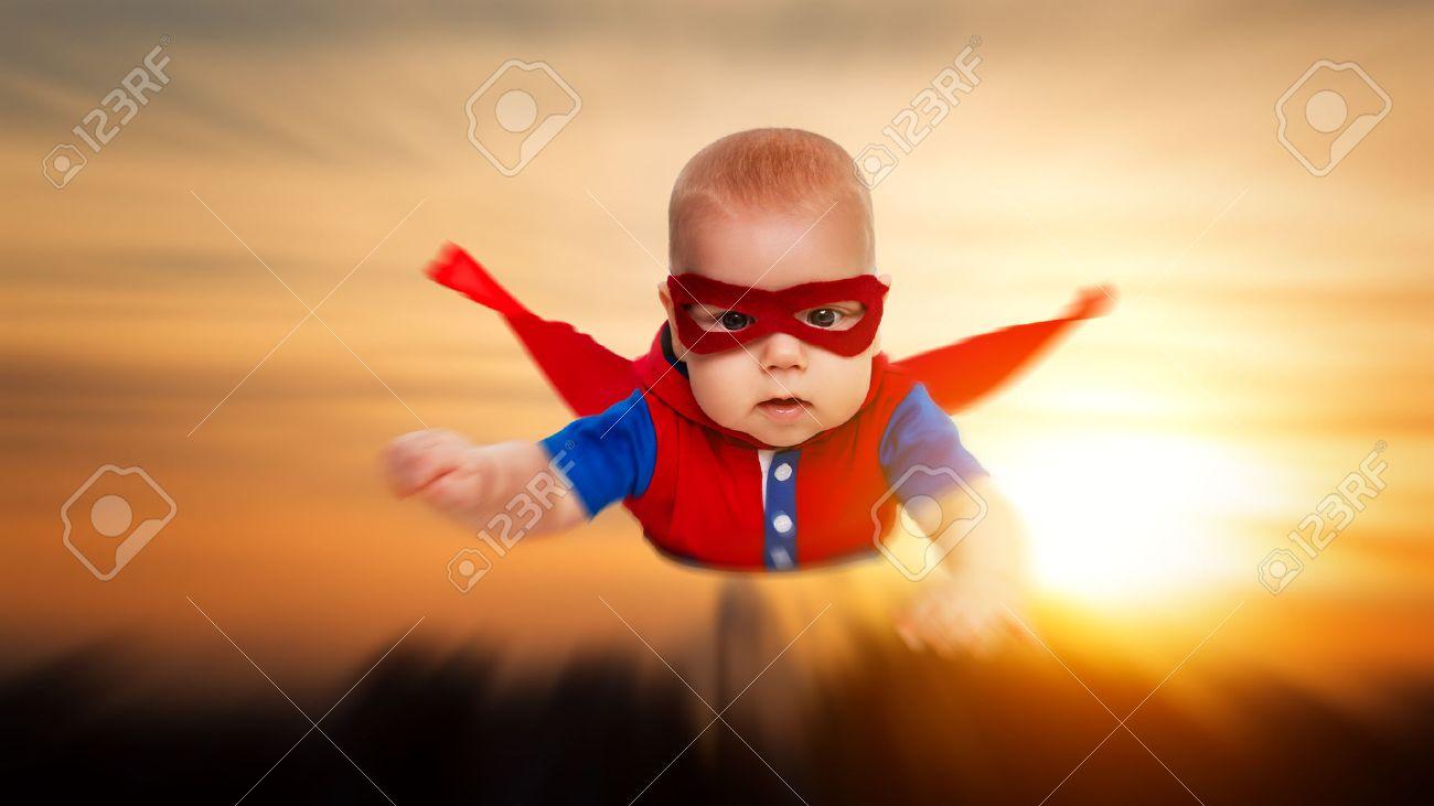 niño pequeño poco superhighway bebé con una capa roja volando por el cielo Foto de archivo - 55011121