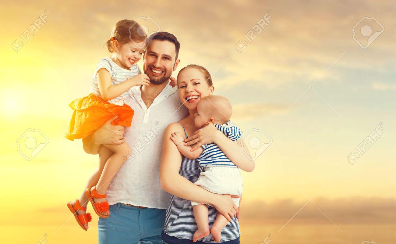 feliz familia de padre, madre y dos hijos, hijo e hija bebé en la playa al atardecer Foto de archivo - 57835381