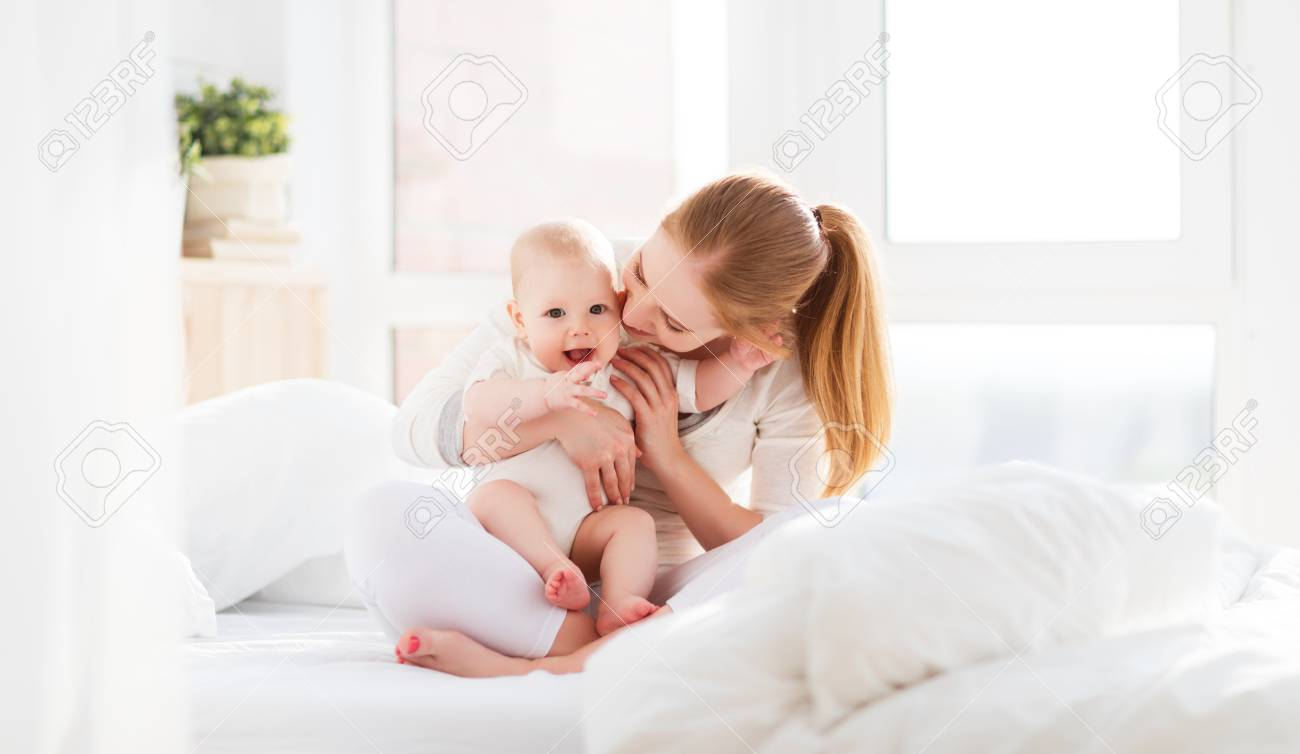 Happy family mother playing and hug with newborn baby in bed stock photo 59145200