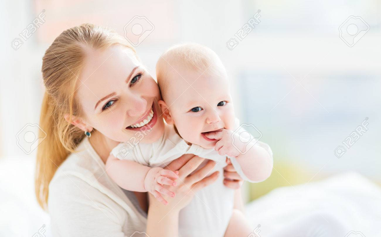 Happy family mother playing and hug with newborn baby in bed stock photo 59145199