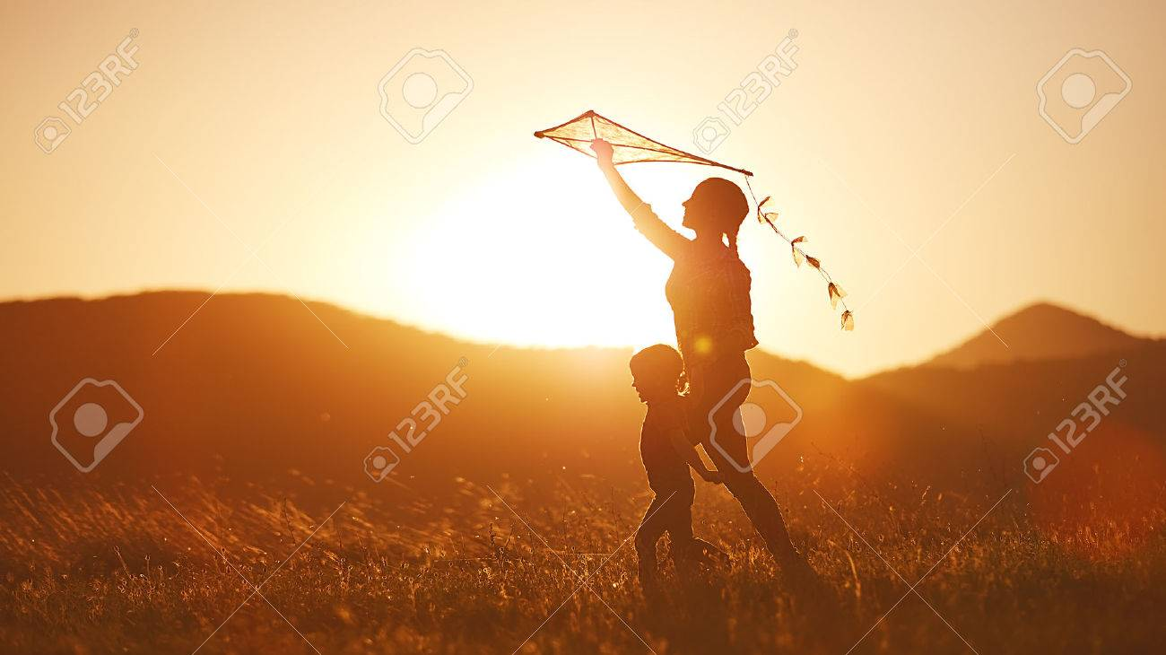 happy family mother and child run on meadow with a kite in the summer on the nature Foto de archivo - 60028142