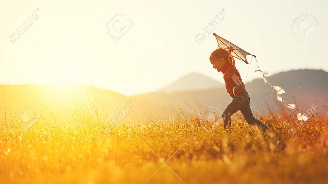 happy child girl with a kite running on meadow in summer in nature - 60028143