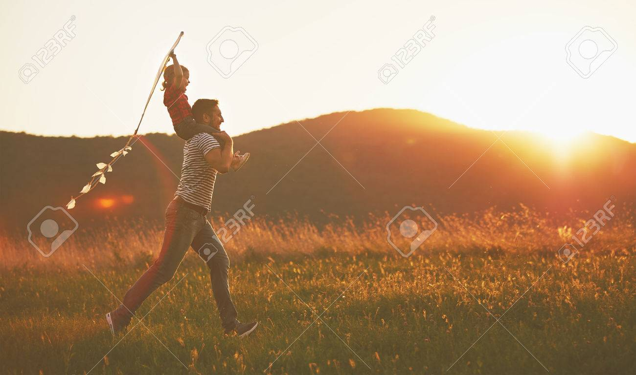 happy family father and child run on meadow with a kite in the summer on the nature - 59422313