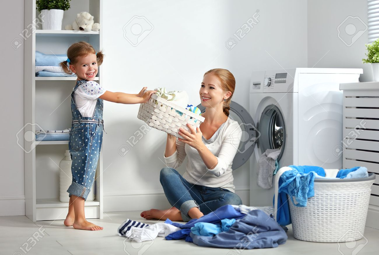 family mother and child girl little helper in laundry room near washing machine and dirty clothes - 61805861