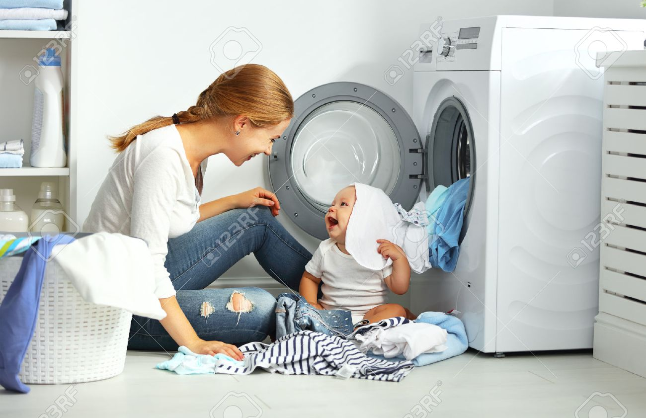 mother a housewife with a baby engaged in laundry fold clothes into the washing machine Foto de archivo - 62010003