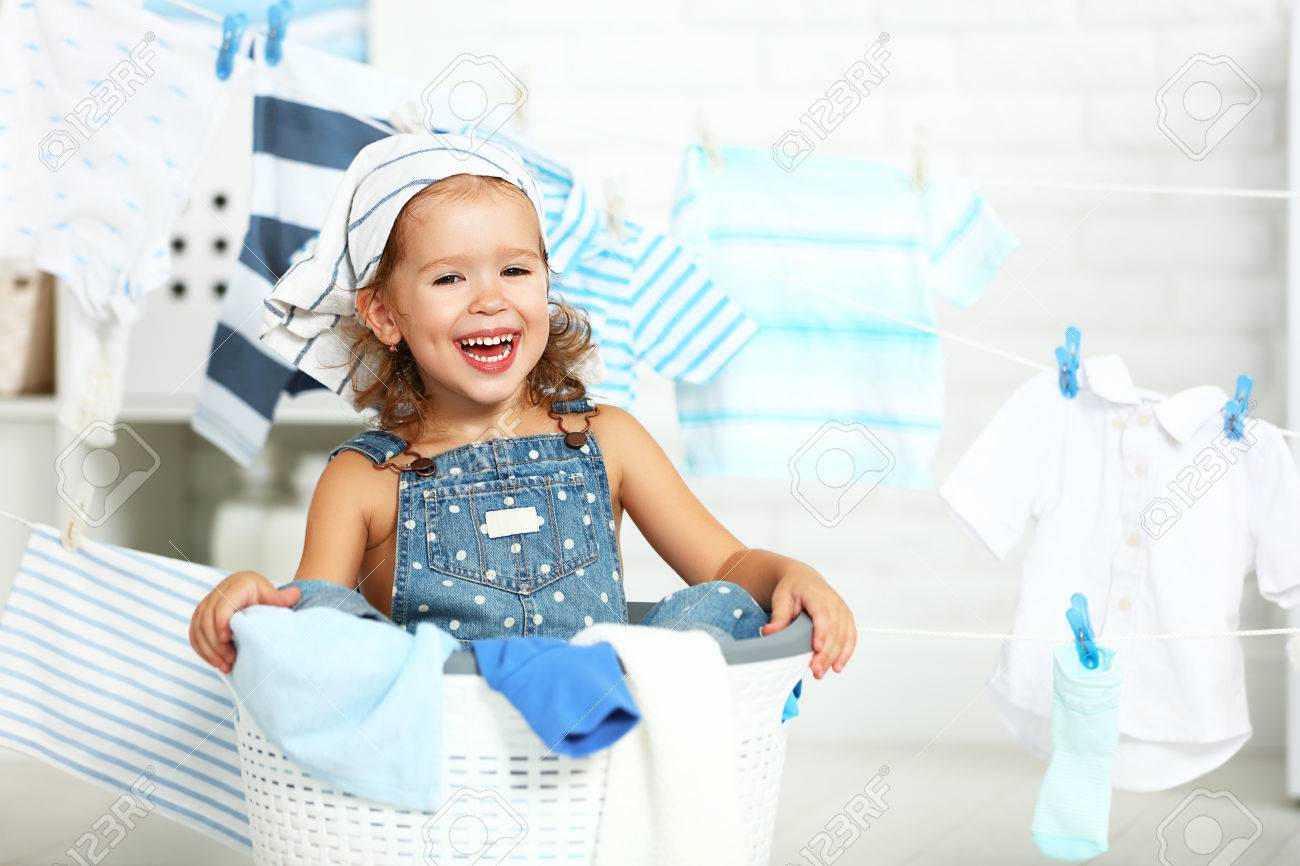 child fun happy little girl  to wash clothes and laughs in the laundry room Foto de archivo - 62010479