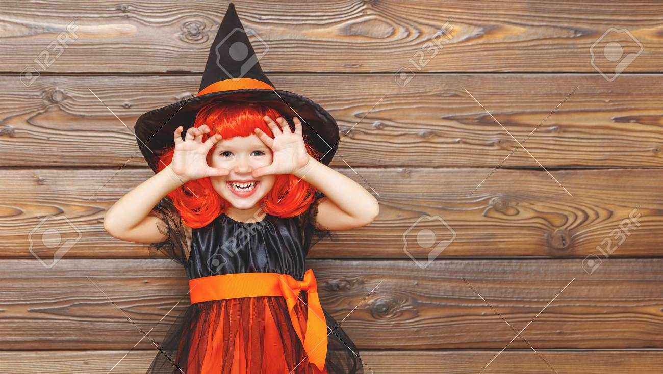 funny child girl in witch costume for Halloween scares on a dark wooden background Stock Photo  sc 1 st  123RF.com & Funny Child Girl In Witch Costume For Halloween Scares On A Dark ...