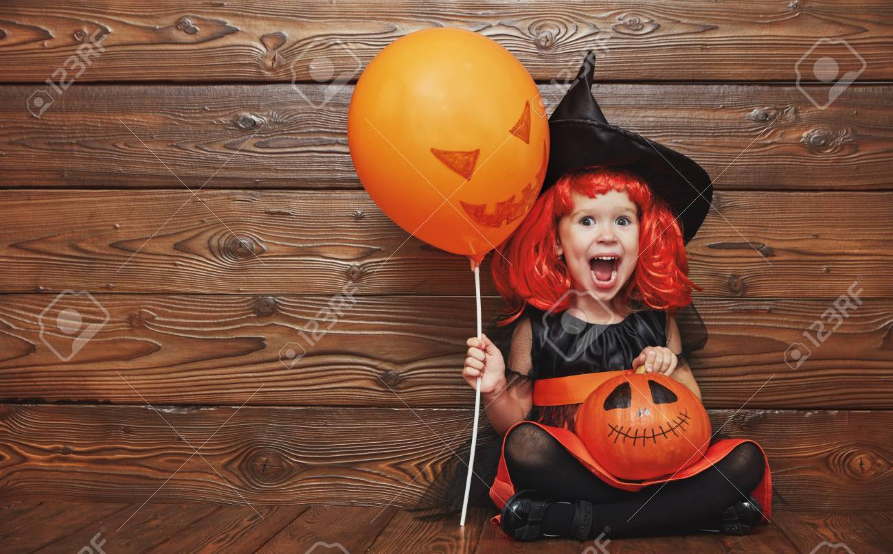 funny child girl in witch costume for Halloween with pumpkin Jack and orange balloon on a dark wooden background - 63077053