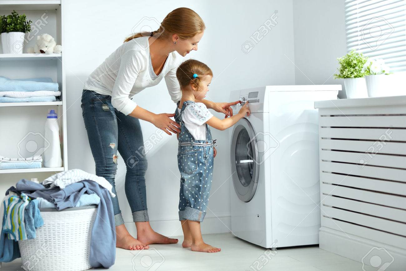 family mother and child girl little helper in laundry room near washing machine and dirty clothes - 64792523