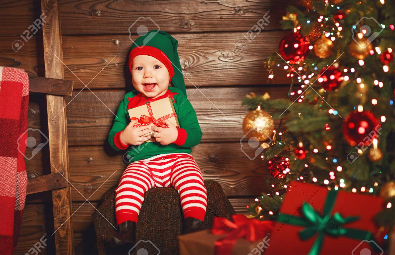Happy baby elf helper of Santa in costume Santa Claus with gift at christmas tree Stock  sc 1 st  123RF.com & Happy Baby Elf Helper Of Santa In Costume Santa Claus With Gift ...