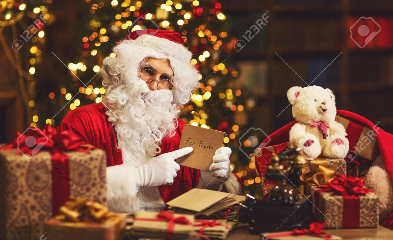 Santa Claus At Desk With Letters Toys Gifts Near Christmas Stock
