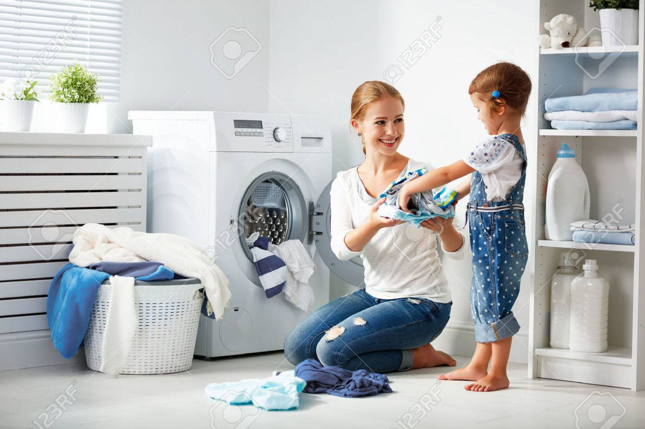 family mother and child girl little helper in laundry room near washing machine and dirty clothes Foto de archivo - 67420719