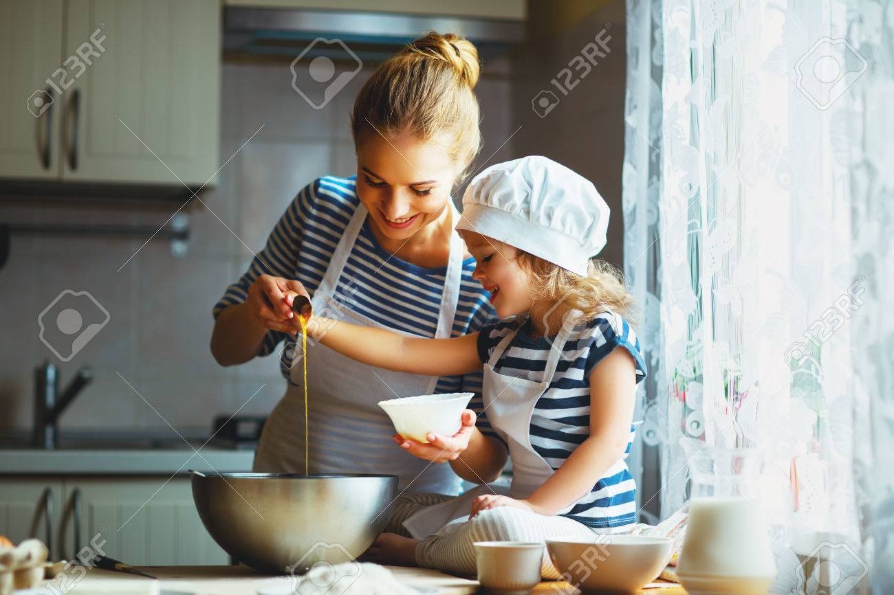 happy family in the kitchen. mother and child daughter preparing the dough, bake cookies - 70173180
