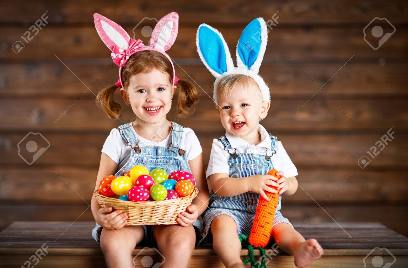 Happy kids boy and girl dressed as Easter bunnies laughing with basket of eggs on wooden background Foto de archivo - 73211998