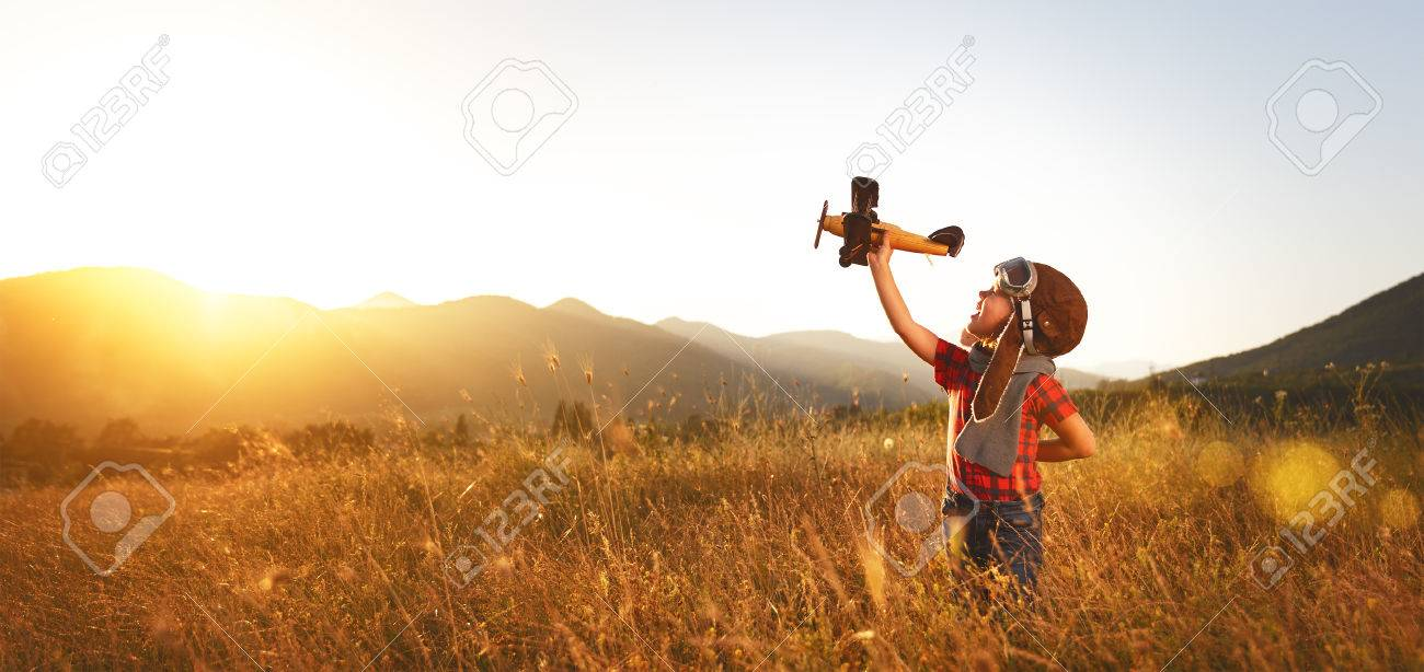 Child pilot aviator with airplane dreams of traveling in summer in nature at sunset Foto de archivo - 74461490