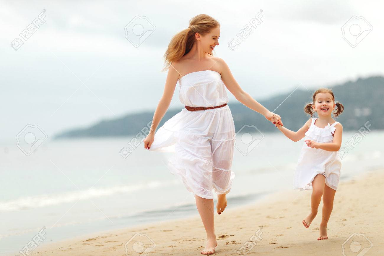 happy family mother and child daughter run, laugh and play at