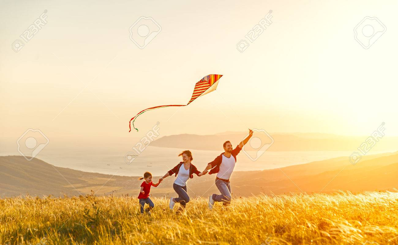 Happy family father of mother and child daughter launch a kite on nature at sunset - 80153636