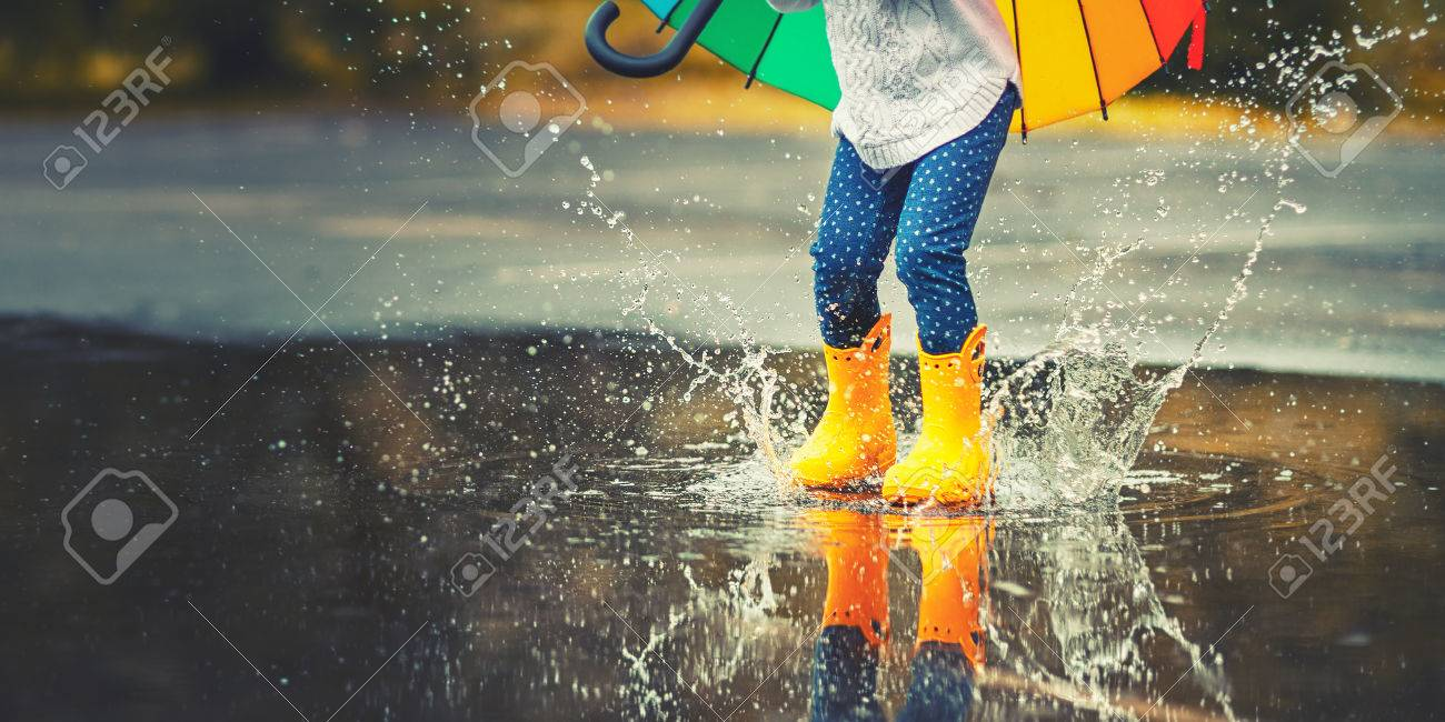 Feet of child in yellow rubber boots jumping over a puddle in..