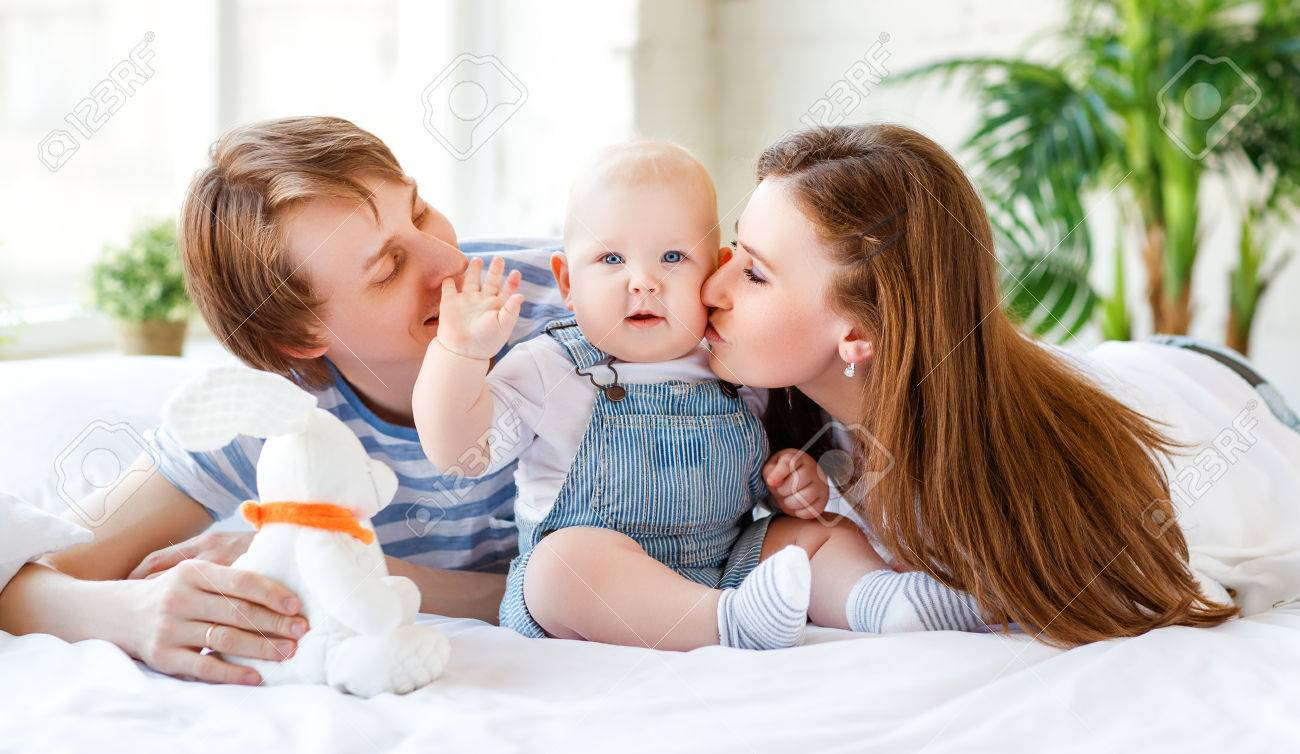 Happy family mother father and baby son in bed stock photo 84168749