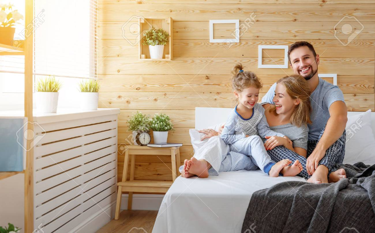 happy family mother, father and child daughter laughs in bed - 86175475