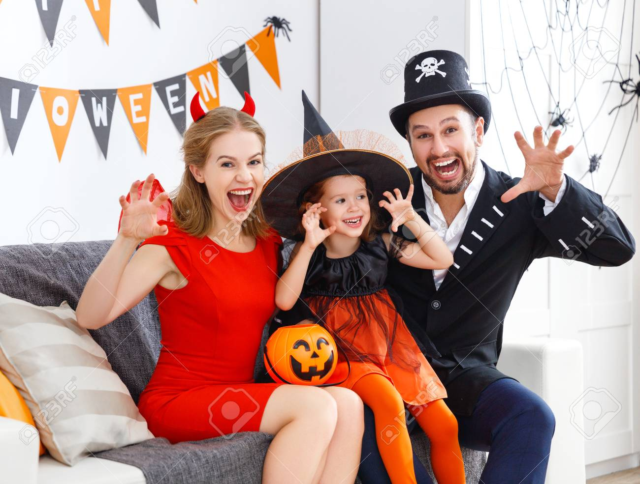 happy family in costumes getting ready for halloween at home - 86199812