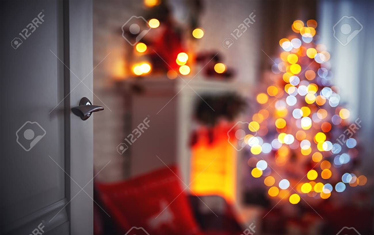 Christmas interior with a Christmas tree fireplace and open door - 89478791