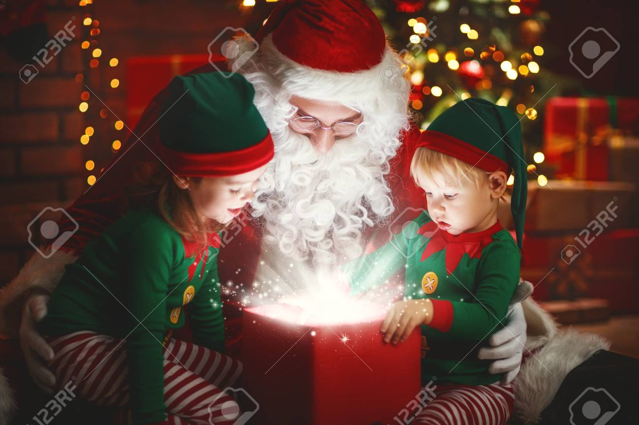 Santa Claus and little elves with a magic gift for Christmas - 89219671