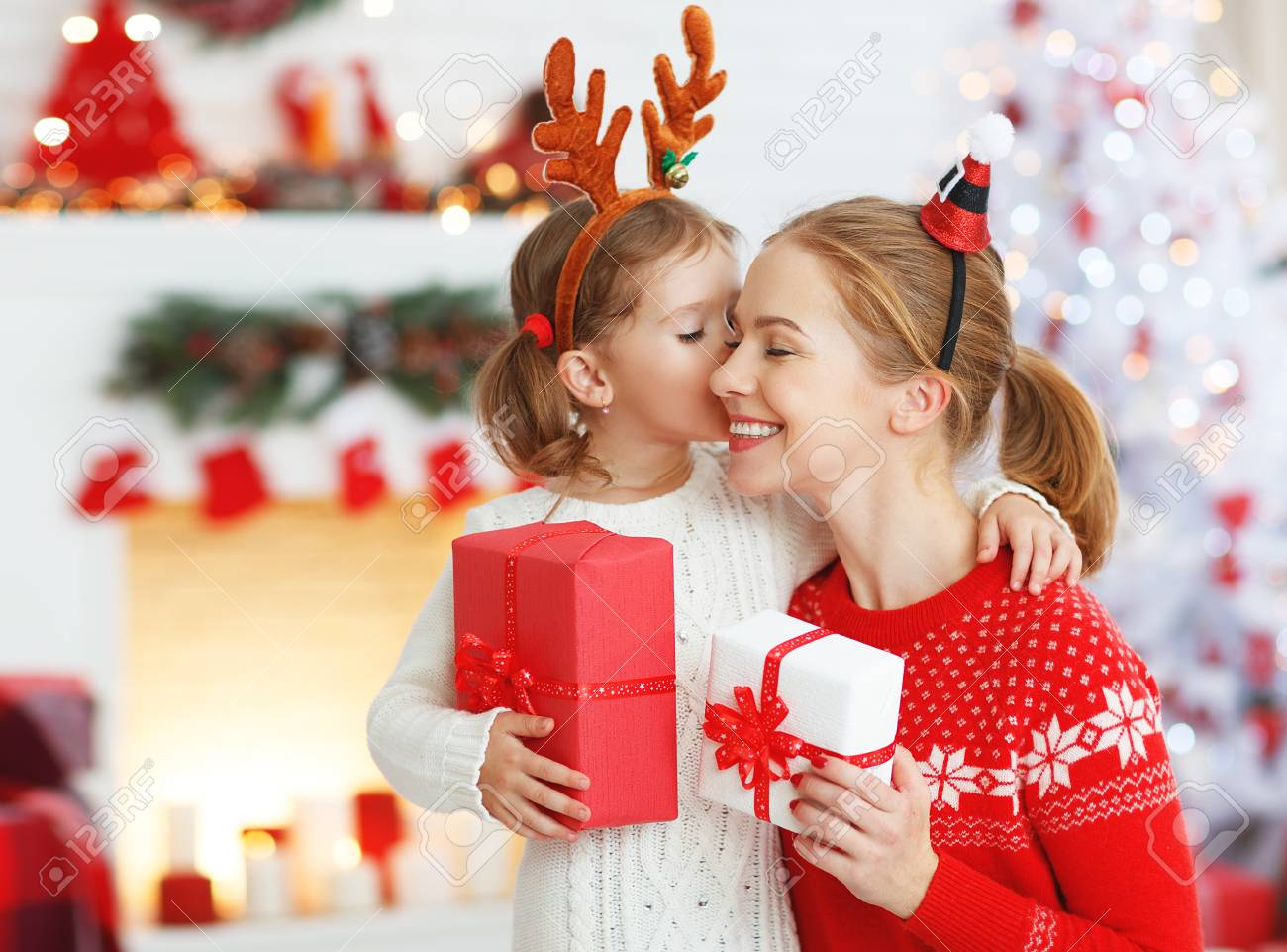 happy family mother and daughter giving christmas gift and embracing - 89274064