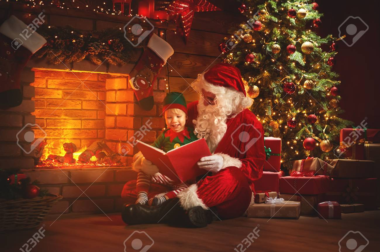 santa claus reads a book to a little elf by fireplace and Christmas tree - 89274071