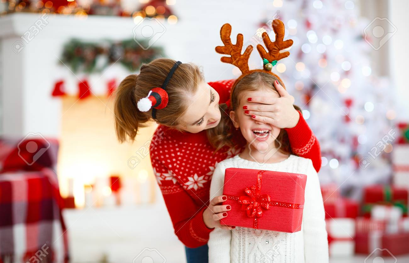 happy family mother and daughter giving christmas gift and embracing - 89274101