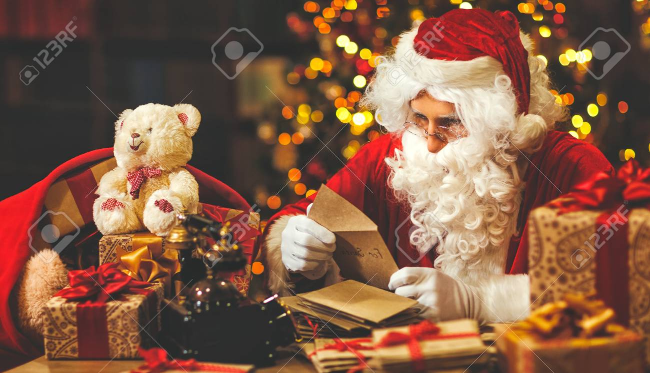 santa claus at his desk with letters and christmas presents stock photo 89291560 - Santa Claus Presents