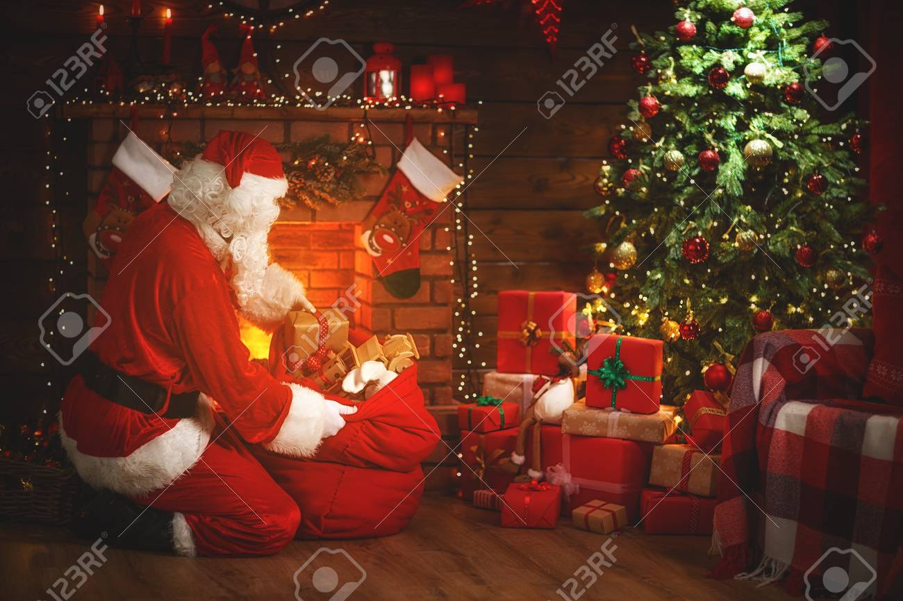 merry christmas santa claus near the fireplace and christmas stock photo picture and royalty free image image 89727956 merry christmas santa claus near the fireplace and christmas stock photo picture and royalty free image image 89727956