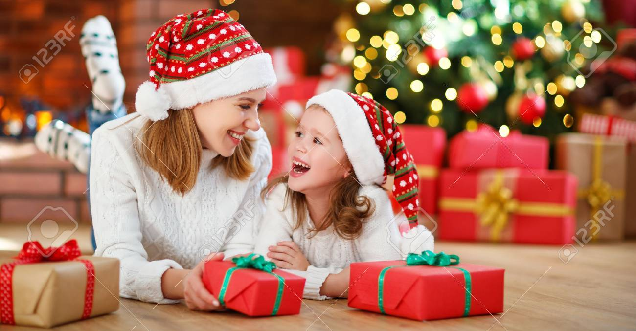 Family Christmas Gift Giving.Happy Family Mother And Daughter Giving Christmas Gift And Embracing