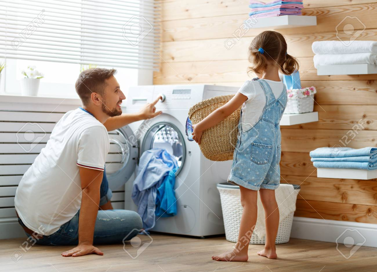 Happy family man father householder and child daughter in laundry with washing machine - 93868286