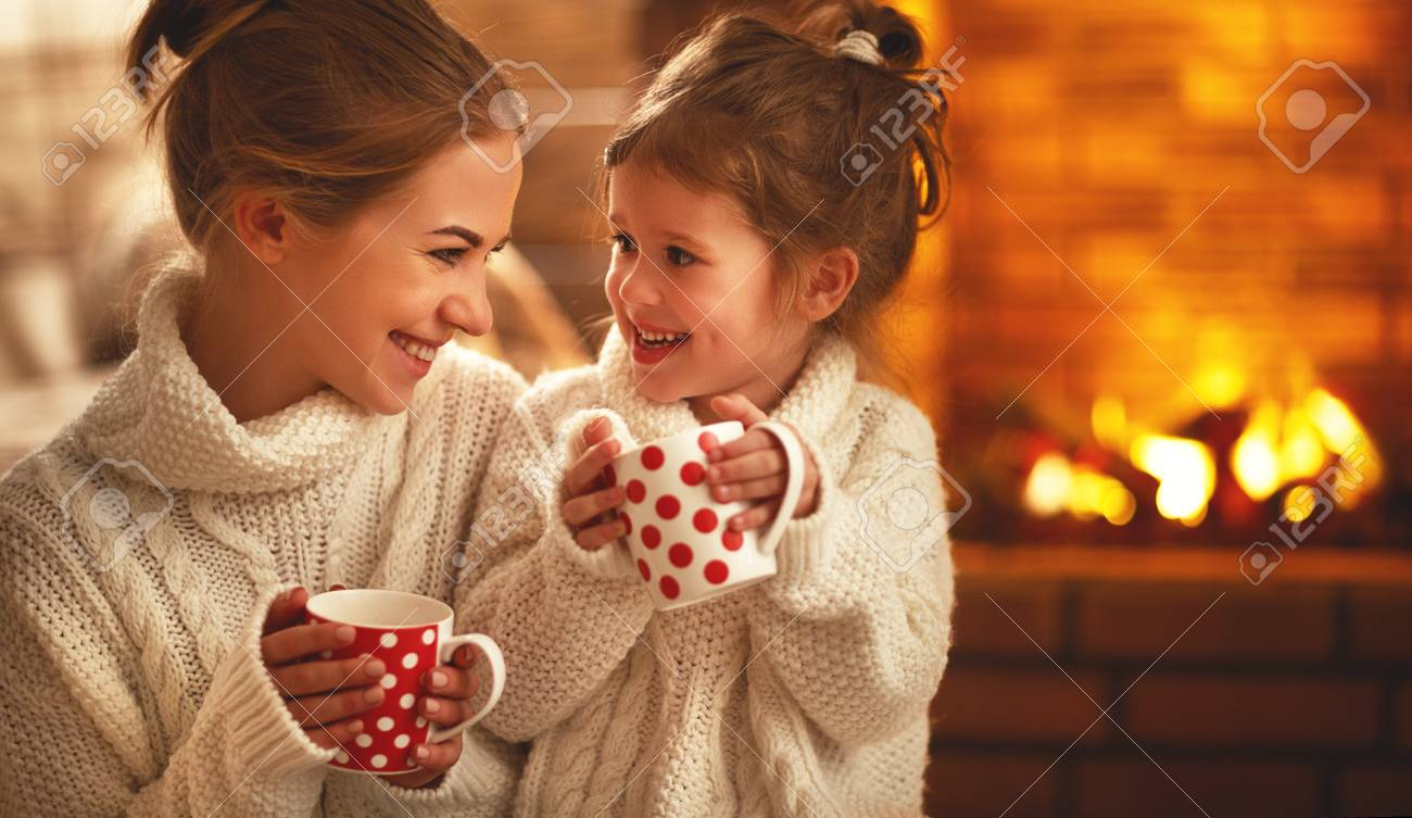 family mother and child daughter drinking tea and laughing on winter evening by fireplace - 93868325