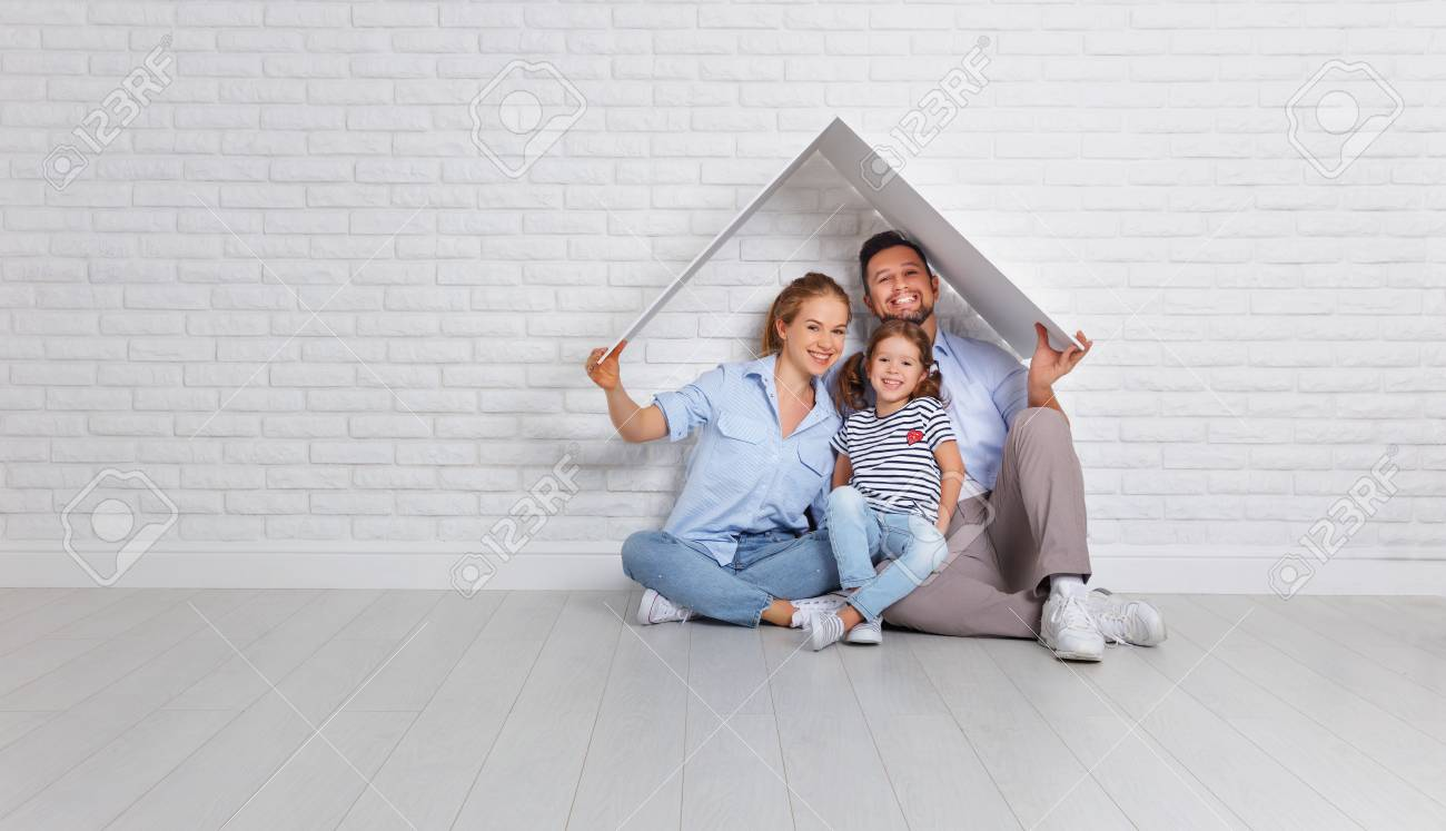 concept housing a young family. Mother father and child in new house with a roof at empty brick wall - 93931143