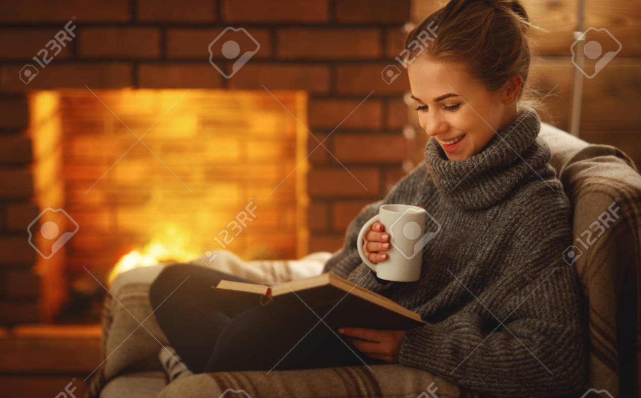 young woman enjoys reading a book by the fireplace on a winter evening - 93931217