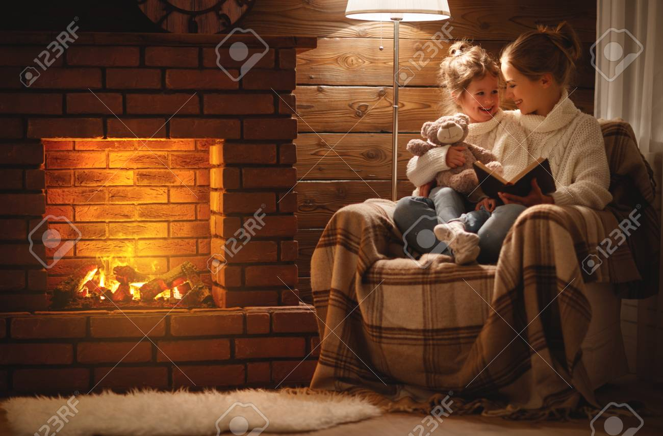 happy family mother and child daughter read a book on winter autumn evening near fireplace - 93931219