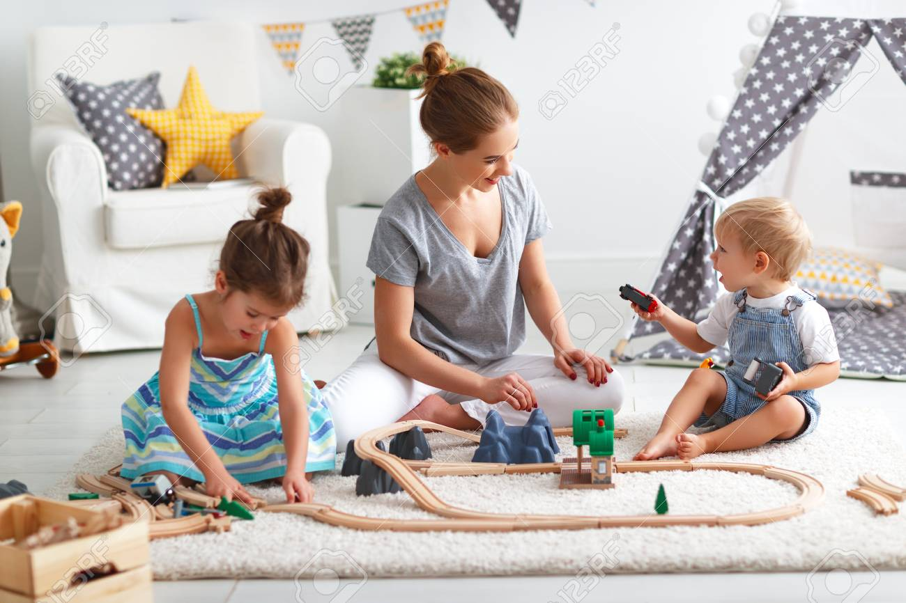 family mother and children play a toy railway in the playroom - 94317960