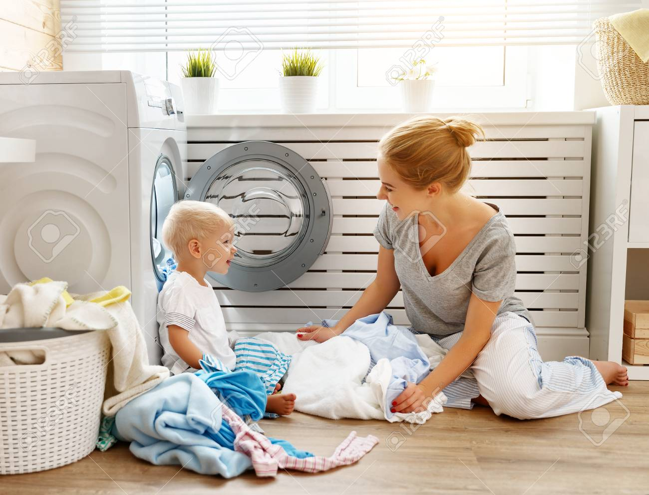 Happy Family Mother Housewife And Child Baby Son In The Laundry