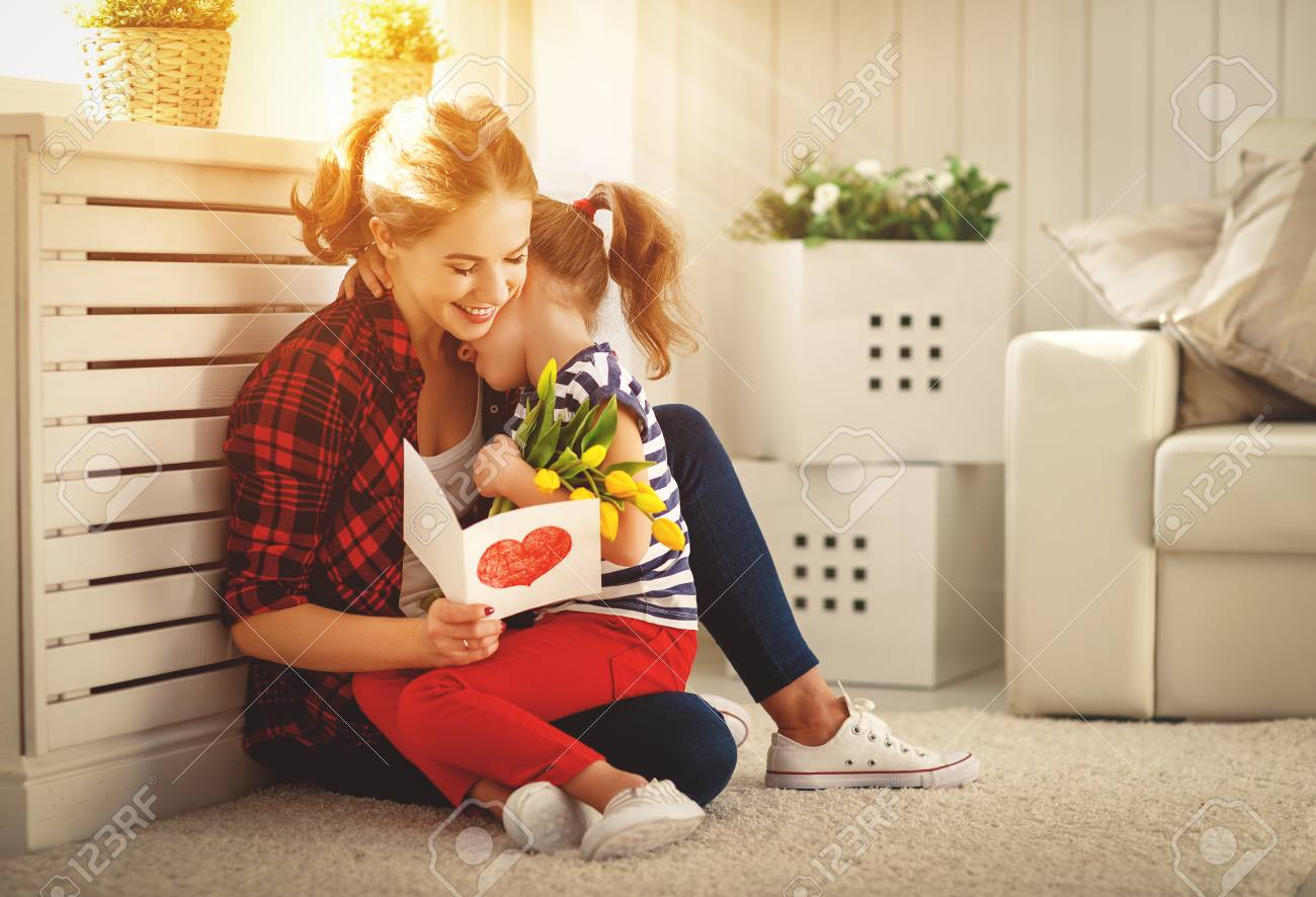 Happy mother's day! Child daughter congratulates moms and gives her a postcard and flowers tulips - 97046504