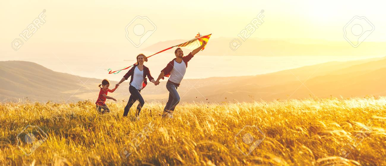 Happy family father, mother and child daughter launch a kite on nature at sunset - 97757778