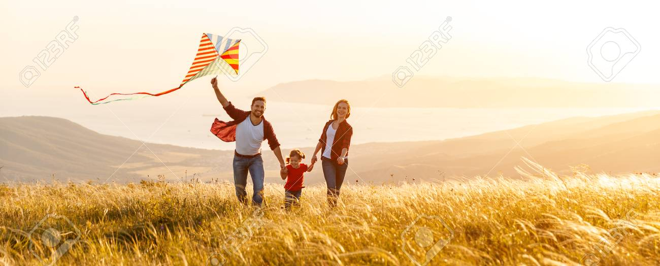 Happy family father, mother and child daughter launch a kite on nature at sunset - 97757776